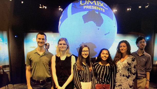 A group of students in front of a globe