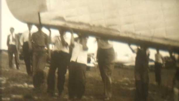 A dated image from the early 20th century of men holding up a row boat.